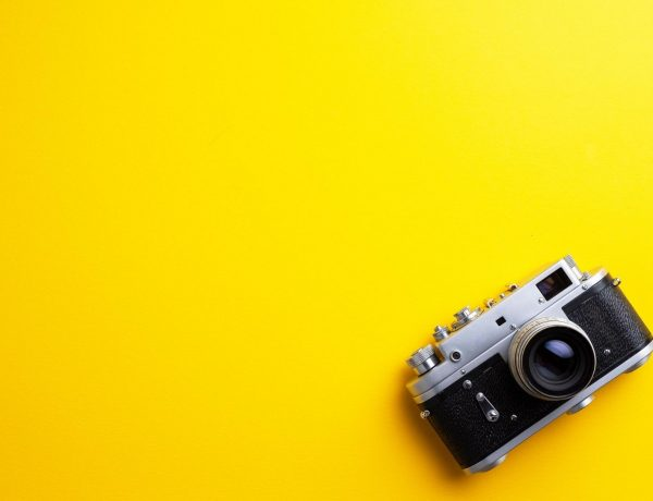 A yellow background with an old school cameral.