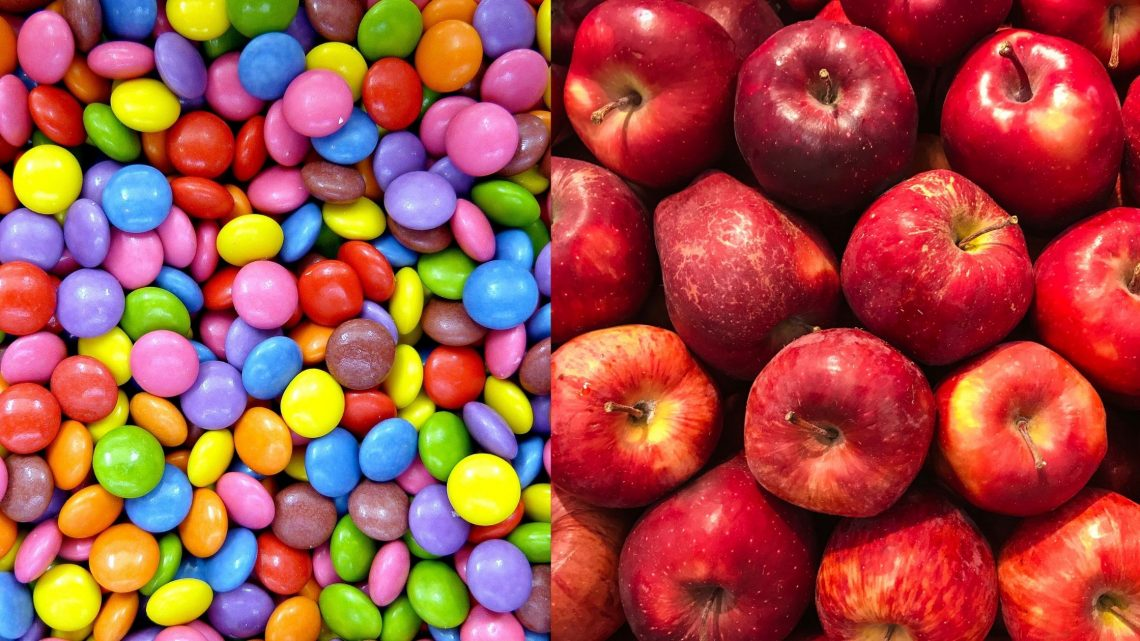 A split-screen image of half little colourful candies and half red apples.